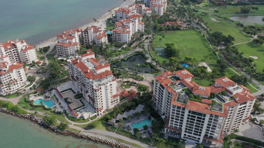 4K aerial view of the prestige residential homes and apartments on the Fisher Island, in Miami suburban area, Florida state. Exclusive real estate with the ocean view. Front line buildings with pools