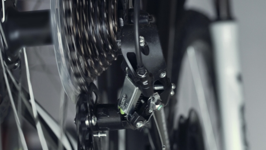 Work of chain drive, rear derailleur with cassette. Changing speeds, gearshift on mountain bike MTB. Chain moves on cogset cogs. Jockey wheels, idler lower and upper pulley. Shift gears. Macro shot | Shutterstock HD Video #1055254133