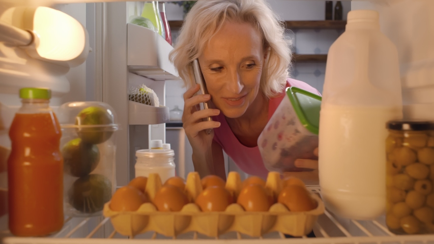Portrait of positive mature woman opening refrigerator and taking plastic container with food talking on mobile phone at home kitchen. Housewife take ingredients for meal in fridge