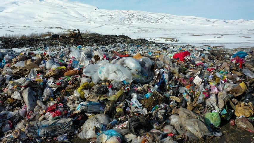 Aerial view garbage, lots of plastic bags on the snow, in winter time. Drone fly very low over plastic bottles rubbish and waste, in winter time. Safe nature, global problem. | Shutterstock HD Video #1055260811