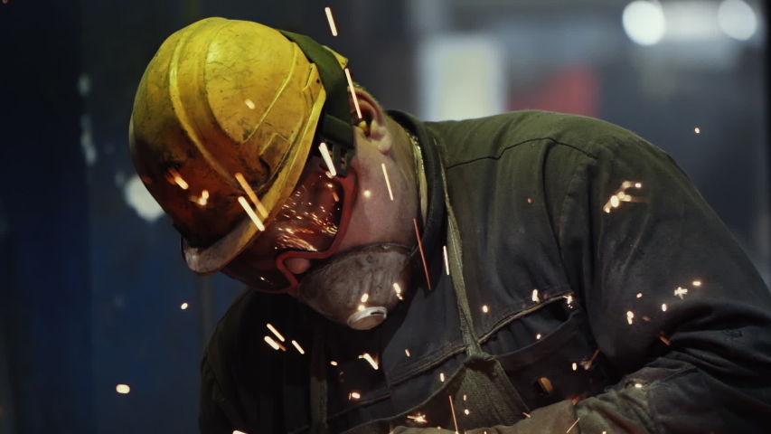 Tough Work of a Welder in Green Uniform and Protection Yellow Helmet at Steel Making Factory. Angle grinder at Metal Production. Sparks, Slow Motion, Close Up