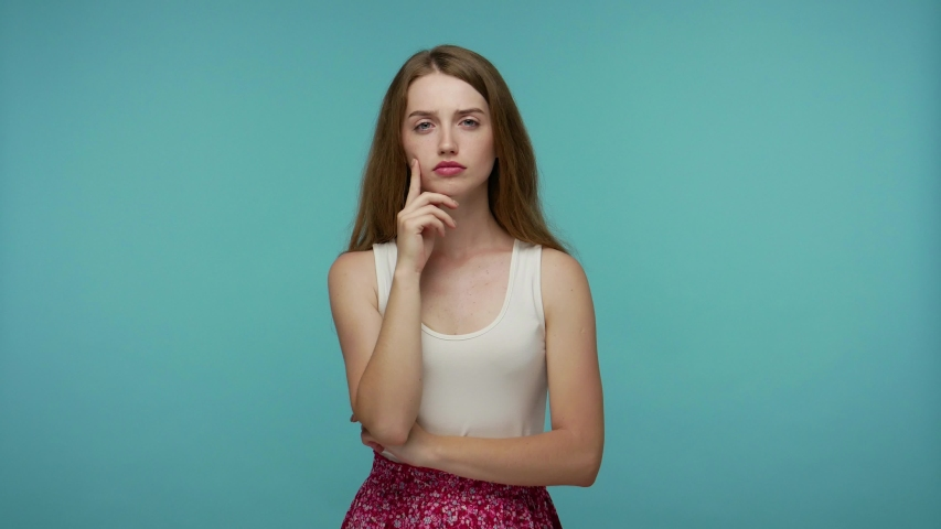 Pensive smart girl rubbing chin and smirking while thinking over idea, imagining plan in mind, having doubts about answer, contemplating and pondering answer. studio shot isolated on blue background Royalty-Free Stock Footage #1055265530