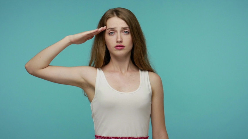 Yes sir! Subordinate, responsible serious girl giving salute listening to order as if soldier, following discipline, obeying, expressing confidence. indoor studio shot isolated on blue background | Shutterstock HD Video #1055265545