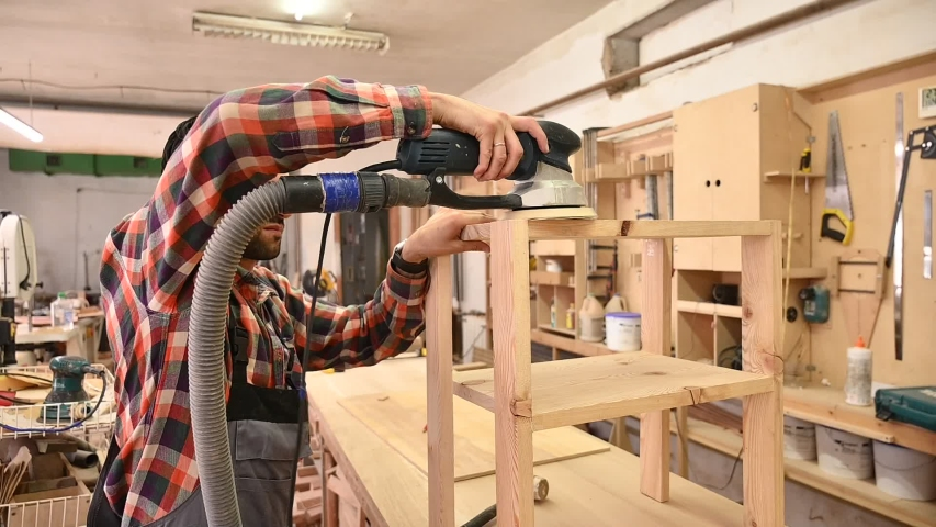Working process in the carpentry workshop.A man Using Electric Sander for wood in a carpentry workshop.Profession, carpentry, woodwork and people concept | Shutterstock HD Video #1055267378