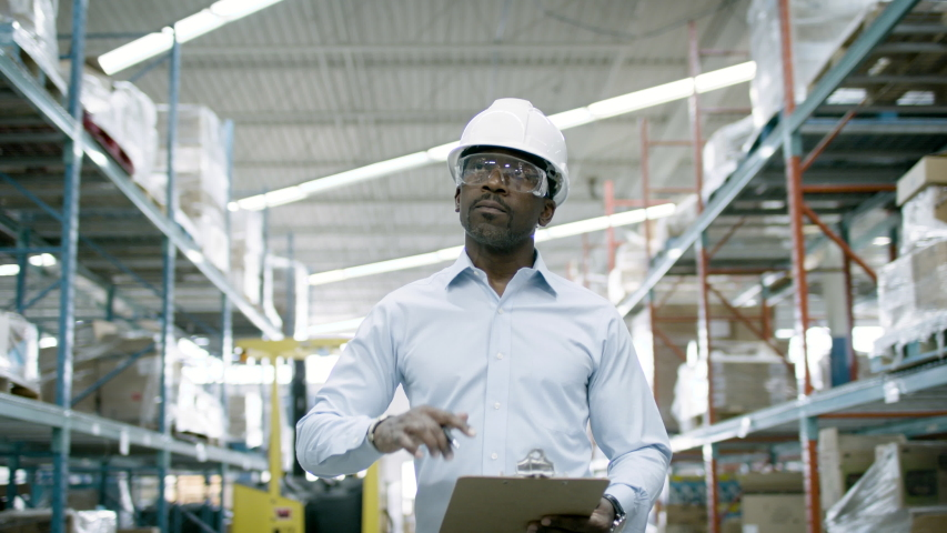 Ecommerce manager looks over inventory and logistics a warehouse facility. Back to work and business is booming. Shot in 4k  | Shutterstock HD Video #1055272367