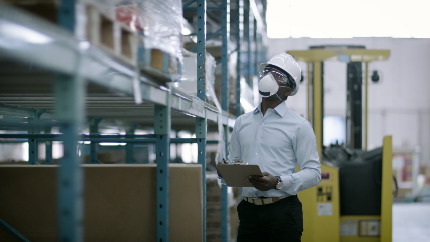 Examining inventory in a mask. A manager checks warehouse safety and inventory. Shot in 4k  | Shutterstock HD Video #1055272442