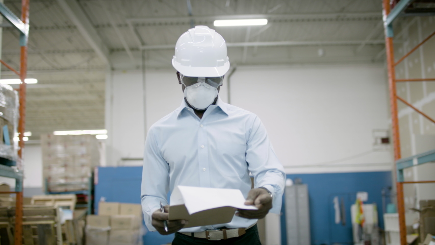 A warehouse manager in a protective mask looks over inventory in an ecommerce facility. Shot in 4k.  Royalty-Free Stock Footage #1055272979