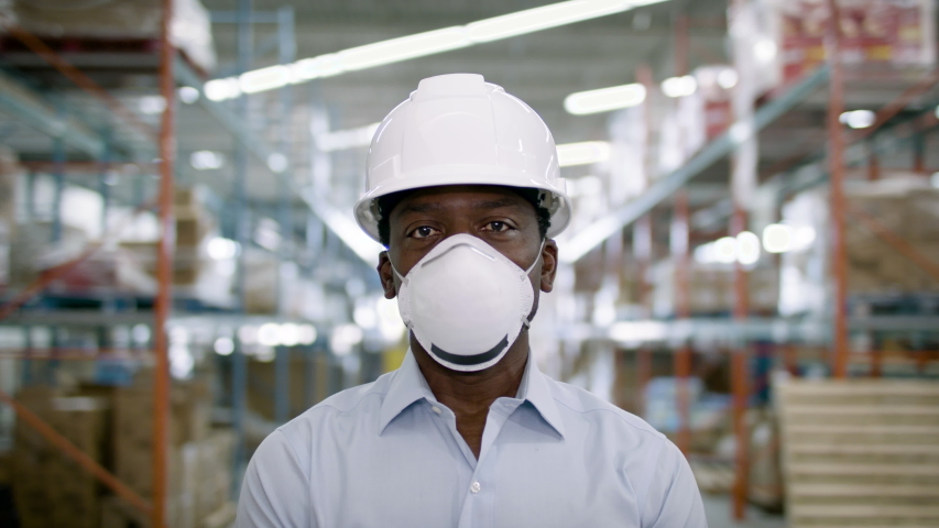 A wearhouse manager in a mask. Supply chain safety. Back to work. Shot in 4k.  Royalty-Free Stock Footage #1055273327