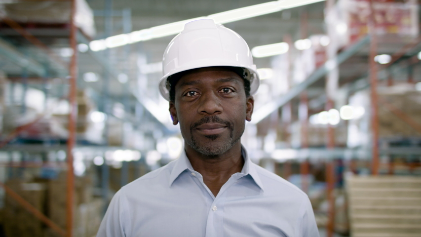 Portrait of a frontline essential worker in a warehouse. Shot in slow-motion and 4k.  Royalty-Free Stock Footage #1055273411