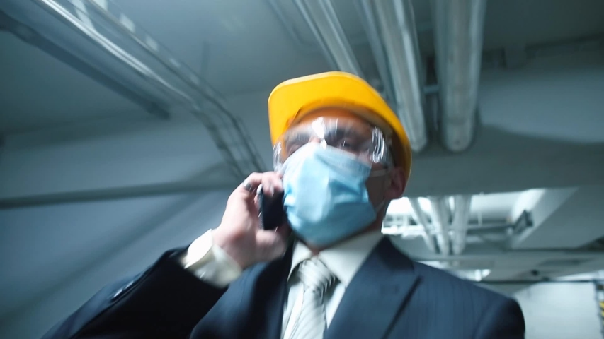 Masked manager face and glasses answers a telephone conversation in garage. Respiratory protection and eye protection in a public place. The crisis of workers in the factory. Search for new employees.