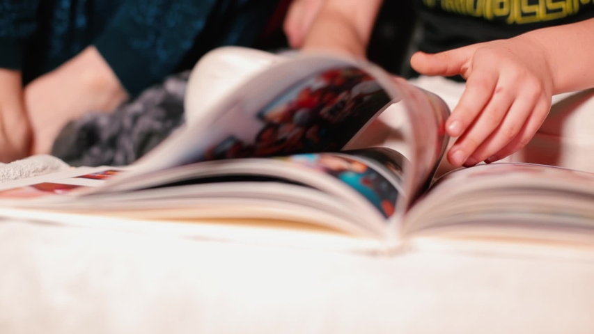 Hands child turning over page book with photos. Living memories positively affects child's self-esteem. Self-isolation of children at home. New knowledge for children without the Internet.    Shutterstock HD Video #1055276081