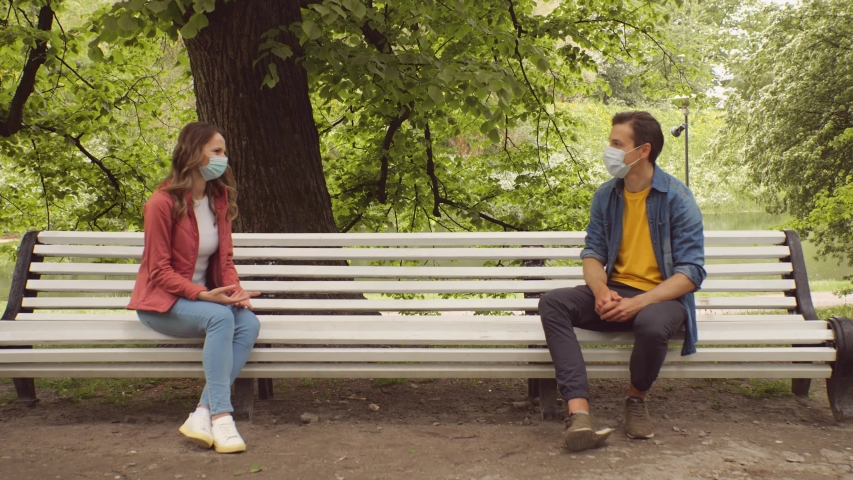 Young, happy, loving couple having date on the bench in the park During the coronavirus lockdown crisis. Relations, friendship and love concept. Social distancing and virus protection.