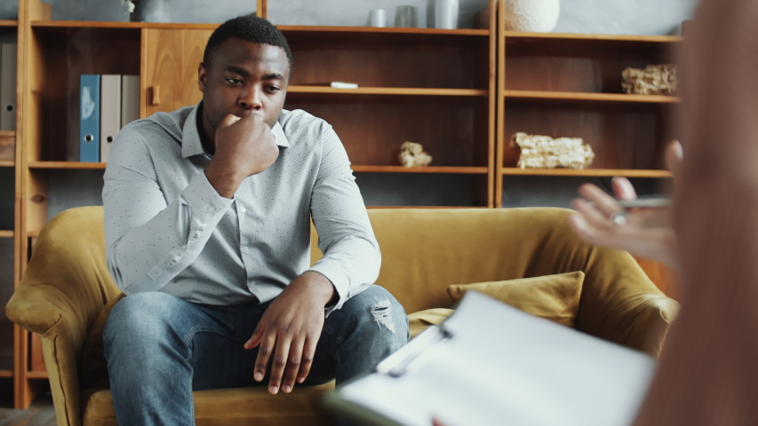 Selective focus shot of unhappy African American man sitting on couch in counseling office and complaining about his troubles to female psychologist while she taking notes on clipboard