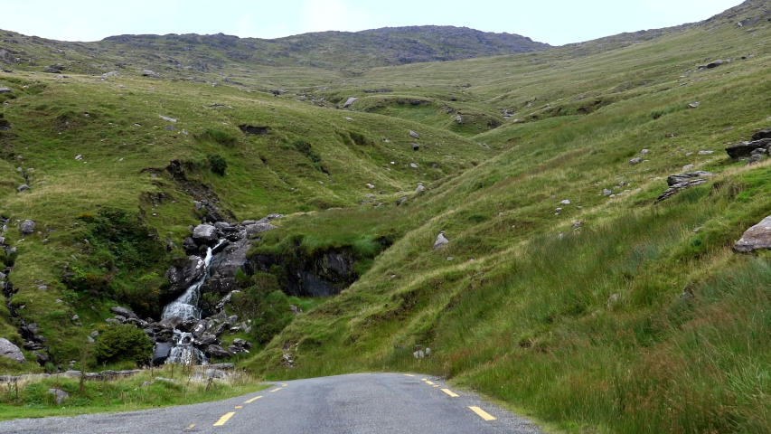 Car front passenger point of view POV driving in Ireland narrow winding road past a small waterfall. | Shutterstock HD Video #1055282108
