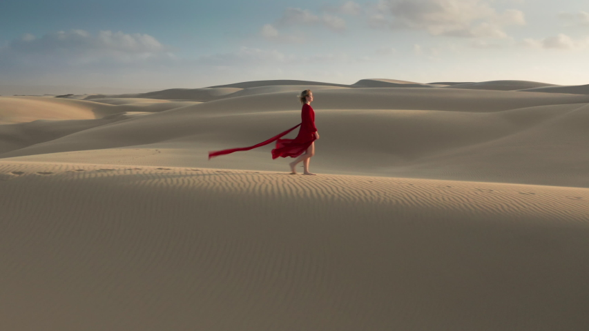 Nature travel aerial video. Young female in a beautiful wavy red dress walking through the natural landscape. 4K Aerial drone footage of a caucasian woman at a windy day, on the sandhill at sunset | Shutterstock HD Video #1055283632