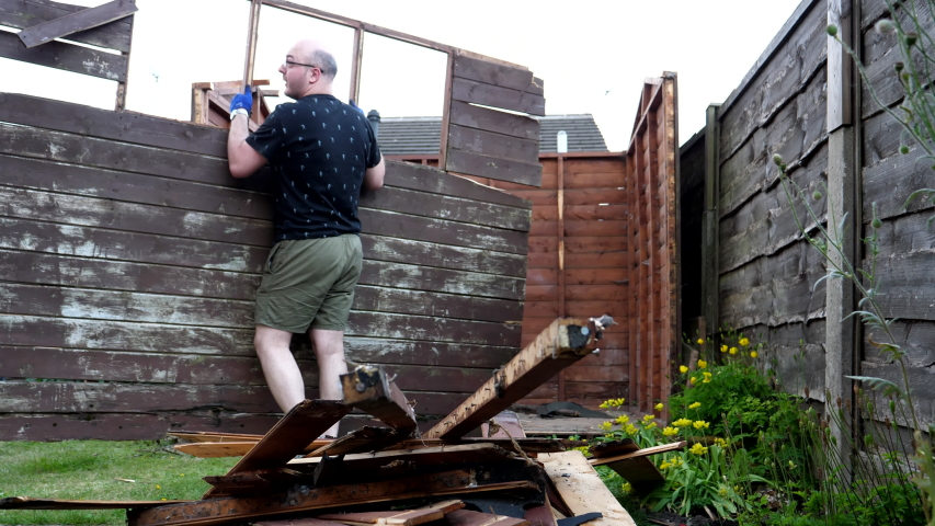 Low angle view of man in shorts and t-shirt breaking down an old rotten back yard storage shed or garden shed in summer. | Shutterstock HD Video #1055284316