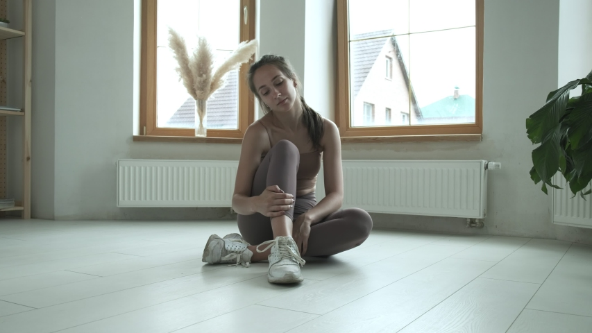Young slim girl in sportswear sitting on floor on knees, untying shoelaces on sneakers. female finishing her work out, running, training at home. sports, fitness, healthy lifestyle, workout exercises