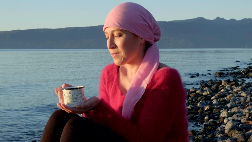 Young breast cancer survivor sitting on the beach drinking a cup of tea while watching the sunset. She's wearing a pink head scarf and a red sweater