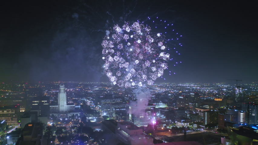 Downtown Los Anges. Aerial view over night cityscape with modern highrises on the front view. The city is beautifully lit with night citylight. Fireworks are seen over the city far on the horizon. 4K