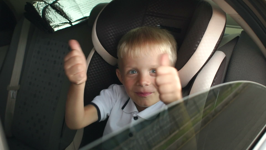 A small cheerful boy sits in a brown child car seat and shows his thumb up. Cute kid is playing and having fun in the kids car seat during the summer journey, slow motion. Child transportation safety. Royalty-Free Stock Footage #1055295635