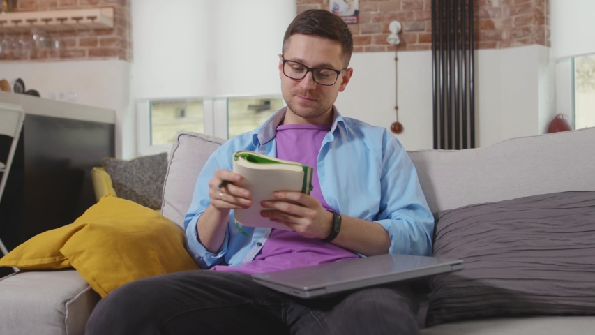 Handsome young man freelancer sitting on sofa use laptop talk and write in a notebook stay at home online working self isolation student online technology from home slow motion | Shutterstock HD Video #1055296973