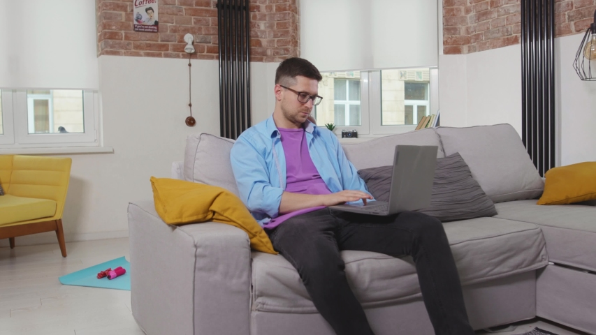 Young man freelancer sitting on sofa use laptop waving his hand no stay at home online working self isolation student online technology from home slow motion | Shutterstock HD Video #1055296976