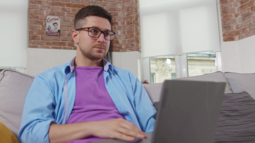 Young man freelancer sitting on sofa thinking use laptop stay at home online working self isolation student online technology from home slow motion | Shutterstock HD Video #1055296979