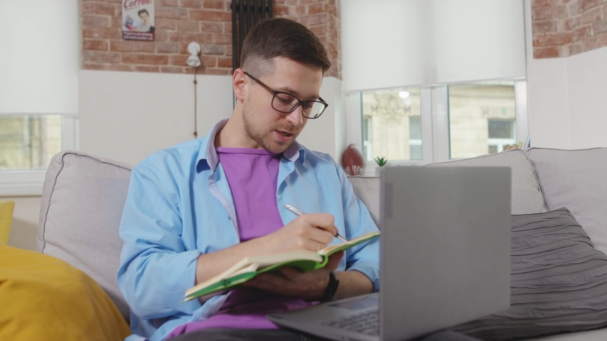 Young man teacher sitting on sofa use laptop talk and write in a notebook speaking on video call stay at home online working self isolation student online technology from home slow motion | Shutterstock HD Video #1055296982
