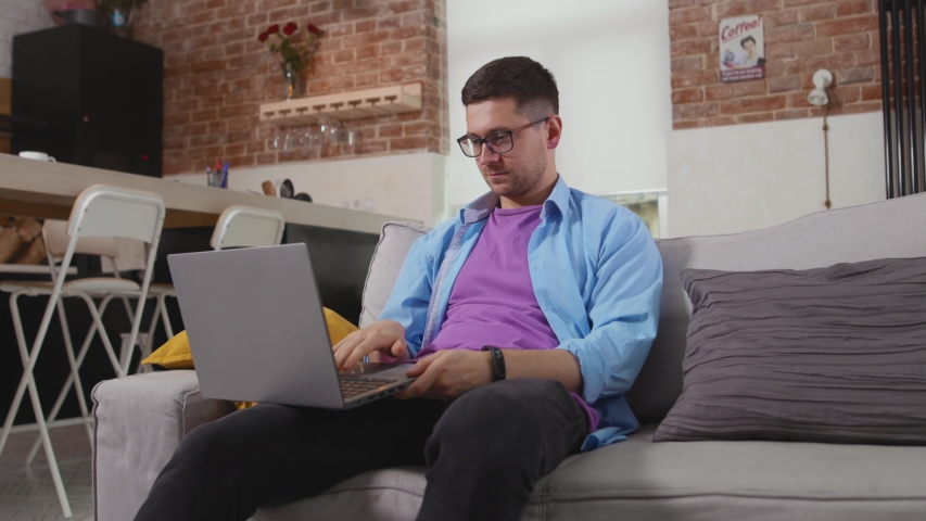 Close up man freelancer sitting on sofa use laptop shows thumb down at home online working self isolation student online technology from home slow motion | Shutterstock HD Video #1055297036