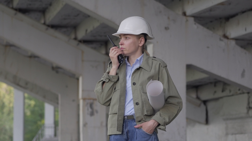 A female worker talks on a radio at a construction site | Shutterstock HD Video #1055297084