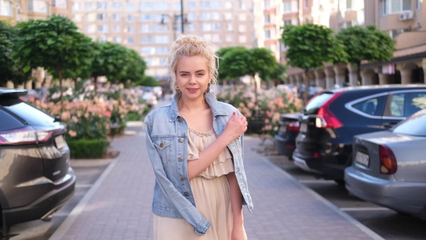 Young blond posing on the city centre  happy and smiling woman | Shutterstock HD Video #1055297708