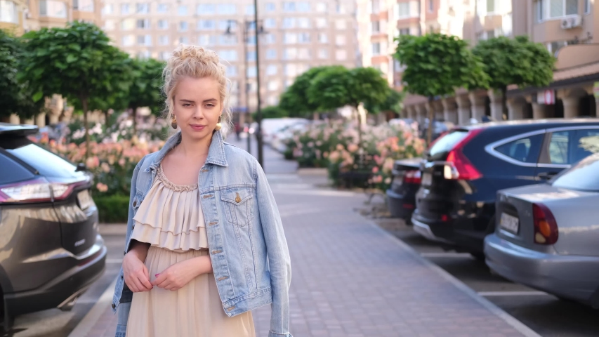 Young blond posing on the city centre  happy and smiling woman | Shutterstock HD Video #1055297711