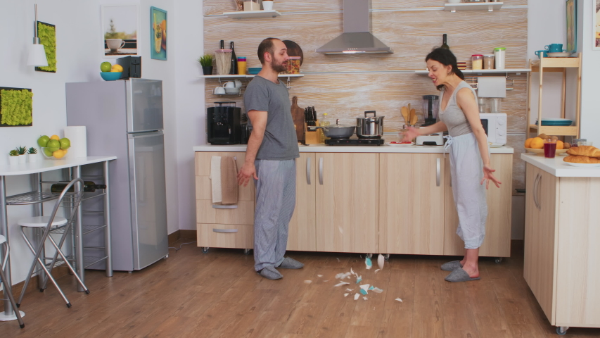Angry wife smashing dish in an argument with husband. Frustrated upset unhappy married woman swearing, smashing dishes, making scandal. Spouse arguing with passion, disagreement conflict and Royalty-Free Stock Footage #1055298560