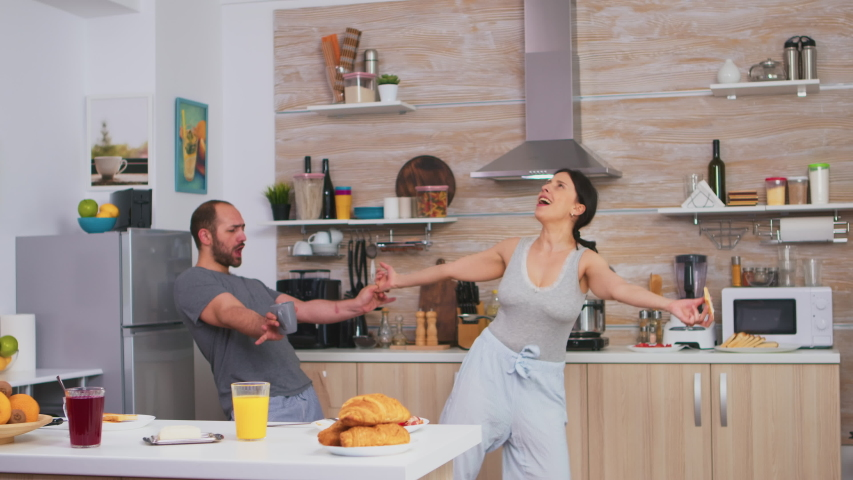 Cheerful couple dancing in kitchen and having fun during breakfast. Carefree husband and wife laughing, singing, dancing listening musing, living happy and worry free. Positive people #1055298593