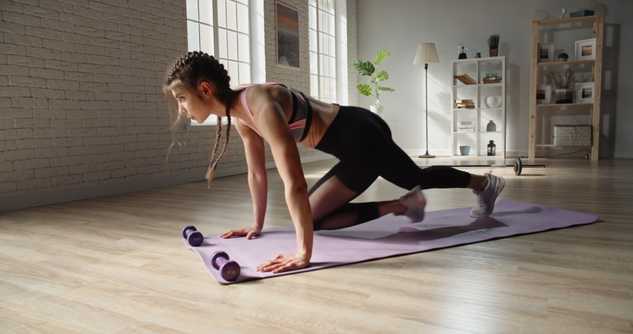 Young fit slimming sportswoman does running plank as part of training. Motivated female athlete working out at home, achieving her goals - sports, healthy lifestyle concept 4k footage | Shutterstock HD Video #1055298707