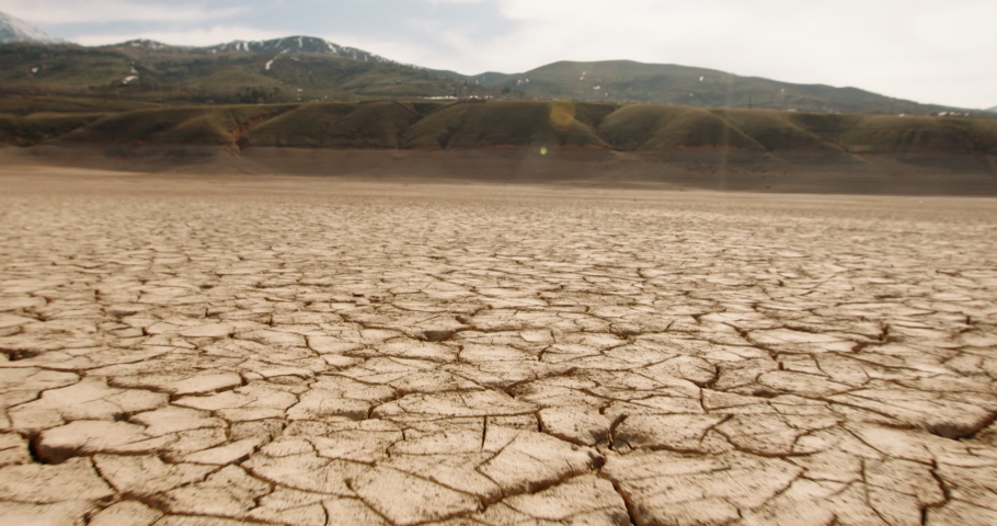 Dynamic shot of cracked soil ground of dried lake or river in mountains. Land destroyed by erosion and global warming - ecological issues concept 4k footage Royalty-Free Stock Footage #1055298752