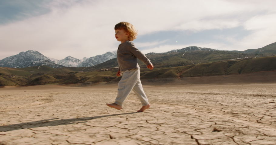 Funny caucasian baby boy running on deserted ground. Cracked soil land after erosions and desertification - ecology, save our planet concept 4k footage Royalty-Free Stock Footage #1055298755
