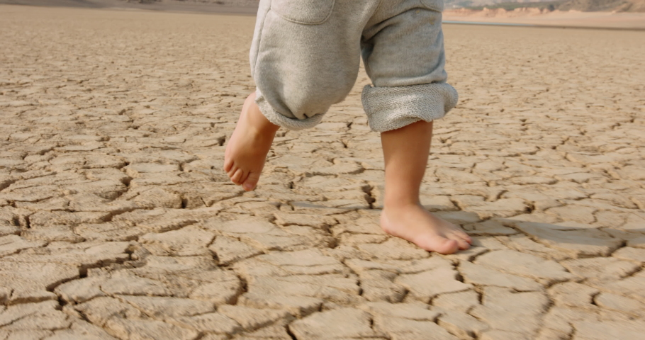 Close up shot of legs of baby boy running on cracked soil, destroyed by overuse, climate change and flood - ecological issues, save our planet 4k footage Royalty-Free Stock Footage #1055298758