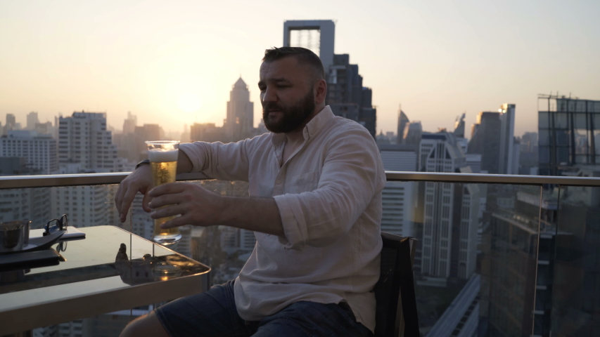 Happy man raising toast with beer at luxury rooftop bar | Shutterstock HD Video #1055299202