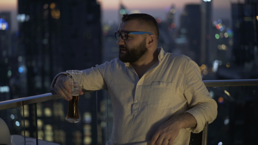 Happy man raising toast with beer at luxury rooftop bar | Shutterstock HD Video #1055299205