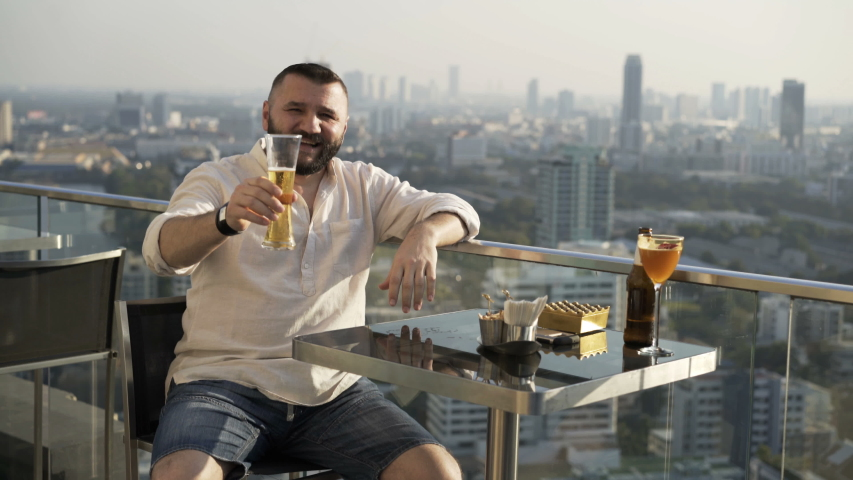 Happy man raising toast with beer at luxury rooftop bar | Shutterstock HD Video #1055299208