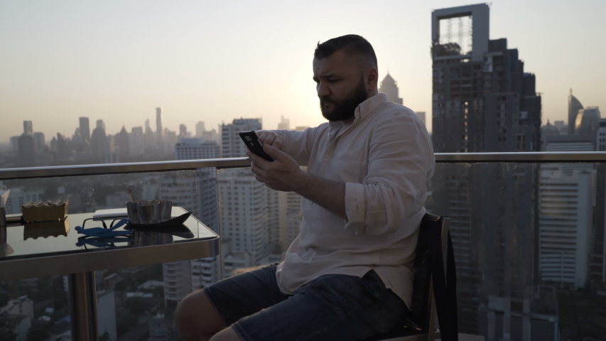 Young man texting on smartphone sitting in luxury rooftop bar | Shutterstock HD Video #1055299223