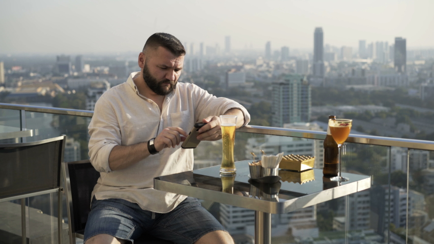 Young man texting on smartphone sitting in luxury rooftop bar | Shutterstock HD Video #1055299226