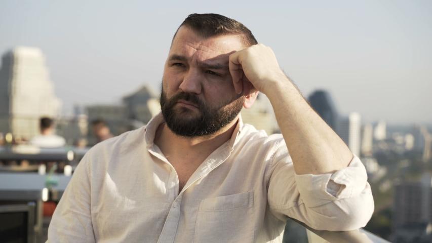 Sad, unhappy man sitting at luxury terrace bar | Shutterstock HD Video #1055299250