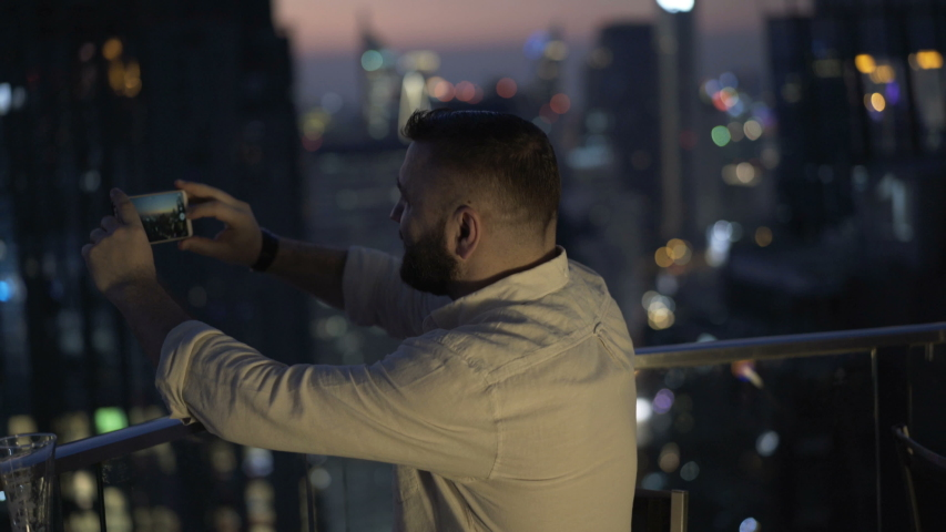 Young man photo of city skyline with smartphone on terrace at night | Shutterstock HD Video #1055299262