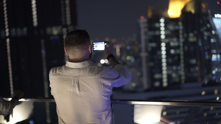 Young man photo of city skyline with smartphone on terrace at night | Shutterstock HD Video #1055299265