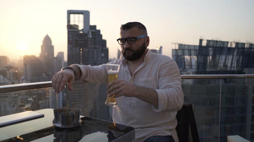 Drunk man drinking beer sitting at luxury bar | Shutterstock HD Video #1055299289