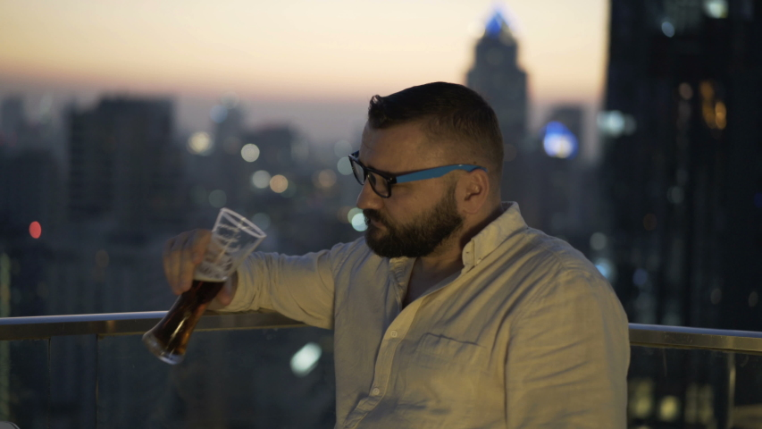 Young pensive, sad man relaxing and drinking beer at luxury bar | Shutterstock HD Video #1055299301