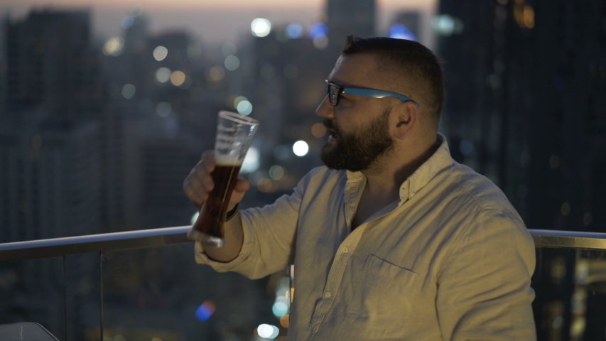 Young happy man relaxing and drinking beer at luxury bar | Shutterstock HD Video #1055299304