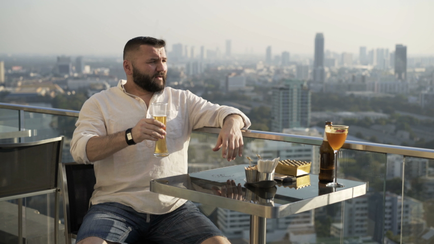 Young happy man relaxing and drinking beer at luxury bar | Shutterstock HD Video #1055299307